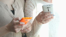 Two girls watching the photos using smartphones stock footage