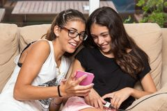 Girls talking about an image they see on the mobile. Two girls watching a picture on the phone, both smile and look like converts Royalty Free Stock Photos