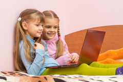 Two girls watching something funny. In notebook stock photo
