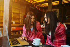 Two girls watching something in laptop. Two young and beautiful girl sitting at the table and looking for something on the Internet Royalty Free Stock Image