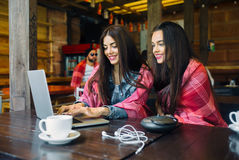 Two girls watching something in laptop. Two young and beautiful girl sitting at the table and looking for something on the Internet Royalty Free Stock Photos
