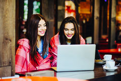 Two girls watching something in laptop. Two young and beautiful girl sitting at the table and looking for something on the Internet Stock Photography