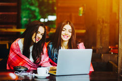 Two girls watching something in laptop. Two young and beautiful girl sitting at the table and looking for something on the Internet Stock Image