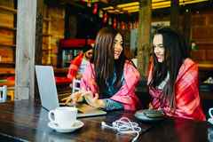 Two girls watching something in laptop. Two young and beautiful girl sitting at the table and looking for something on the Internet Stock Images