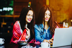 Two girls watching something in laptop. Two young and beautiful girl sitting at the table and looking for something on the Internet Royalty Free Stock Images