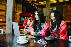 Two girls watching something in laptop. Two young and beautiful girl sitting at the table and looking for something on the Internet Stock Photo