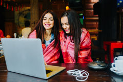 Two girls watching something in laptop. Two young and beautiful girl sitting at the table and looking for something on the Internet Stock Photos