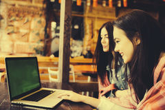 Two girls watching something in laptop. Two young and beautiful girl sitting at the table and looking for something on the Internet,  instagram tone Stock Image