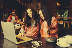 Two girls watching something in laptop. Two young and beautiful girl sitting at the table and looking for something on the Internet,  instagram tone Stock Images