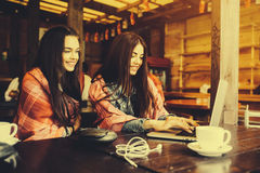 Two girls watching something in laptop. Two young and beautiful girl sitting at the table and looking for something on the Internet,  instagram tone Royalty Free Stock Image