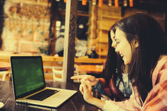 Two girls watching something in laptop. Two young and beautiful girl sitting at the table and looking for something on the Internet,  instagram tone Royalty Free Stock Photos