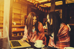 Two girls watching something in laptop. Two young and beautiful girl sitting at the table and looking for something on the Internet,  instagram tone Royalty Free Stock Photo