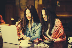 Two girls watching something in laptop. Two young and beautiful girl sitting at the table and looking for something on the Internet,  instagram tone Royalty Free Stock Images