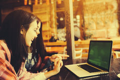 Two girls watching something in laptop. Two young and beautiful girl sitting at the table and looking for something on the Internet,  instagram tone Stock Photo