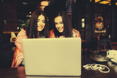 Two girls watching something in laptop. Two young and beautiful girl sitting at the table and looking for something on the Internet,  instagram tone Stock Photography