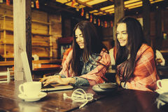 Two girls watching something in laptop. Two young and beautiful girl sitting at the table and looking for something on the Internet,  instagram tone Royalty Free Stock Photography