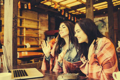 Two girls watching something in laptop. Two young and beautiful girl sitting at the table and looking for something on the Internet,  instagram tone Stock Photos