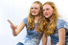 Two girls watching TV. Two teenage sisters holding a remote control and aiming at the TV, isolated on white - grey background Stock Photo