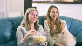 Two girls watching tv together and eating popcorn stock video footage