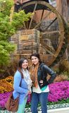 Two girls by a water wheel. Two young, attractive girls standing in front of a water wheel bordered by an array of flowers Royalty Free Stock Image