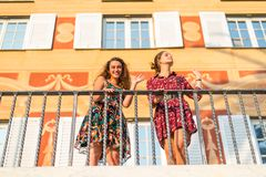 Hi there, how are you. Two girls waving and smiling on top of a tarace, How are you doing stock images