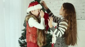 Two girls wear Santa hats to one another stock footage