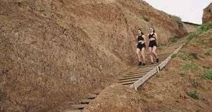Two girls wearing all black sports clothes and speed walk down the stairs onto the sand , they are being healthy stock footage