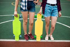 Two girls wearing checkered shirts and denim shorts are standing on the sportsfield with bright longboards in their stock photography