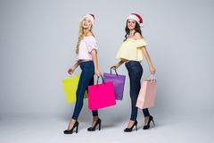 Two girls wearing Christmas hat with bags on white background isolated. Two girls wearing Christmas hat with bags on white background Stock Photography