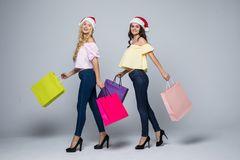 Two girls wearing Christmas hat with bags on white background isolated. Two girls wearing Christmas hat with bags on white background Stock Photo