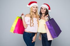Two girls wearing Christmas hat with bags on white background isolated. Two girls wearing Christmas hat with bags on white background Royalty Free Stock Image