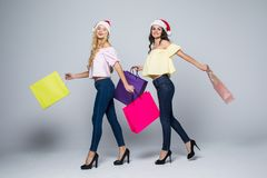 Two girls wearing Christmas hat with bags on white background isolated. Two girls wearing Christmas hat with bags on white background Stock Images