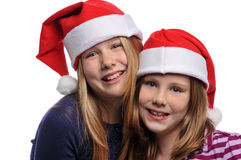 Two girls wearing Christmas hats Royalty Free Stock Photos