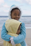 Two girls (5-9) wearing fleeces with hoods, embracing on beach, close-up, smiling, portrait Royalty Free Stock Photos