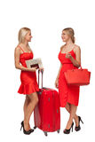 Two girls wearing red dresses with big suitcase and bag Royalty Free Stock Image