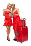 Two girls wearing red dresses with big suitcase and bag and tabl Royalty Free Stock Photography