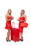 Two girls wearing red dresses with big suitcase and bag and tabl Stock Images