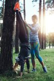 Two girls wearing sportswear training outdoors doing handstand against tree in the park stock photos