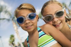 Two girls (7-9) wearing swim goggles portrait. Stock Photography