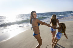 Two girls (5-12) wearing swimwear, pulling mother along sandy beach, woman looking over shoulder, smiling, rear view, sunlight shi. Two girls (5-12) wearing Royalty Free Stock Photo