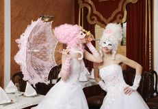 Two girls in wedding dresses and masks Stock Image