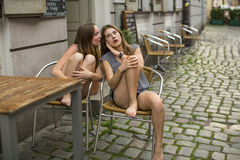 Two girls whispering sitting on the street. Royalty Free Stock Photo