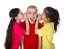 Two girls whispering something to third girl Stock Image