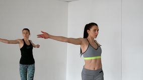 Two girls on a white background in the gym hold a lesson on pilates. Two girls on a white background in the gym hold a lesson on pilates stock footage