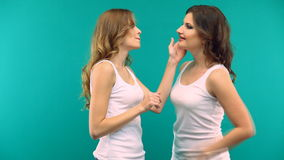 Two girls in white shirts are hugging laughing on a green background stock footage
