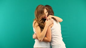 Two girls in white shirts are hugging laughing on a green background stock video footage