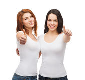 Two girls in white t-shirts showing thumbs up royalty free stock photography