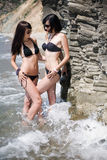 Two girls on wild seashore. Attractive girls in black swimwear are posing in the sea Royalty Free Stock Photos