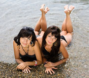 Two girls on wild seashore Royalty Free Stock Photos