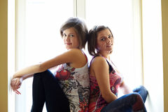 Two Girls on a Windowsill Royalty Free Stock Images